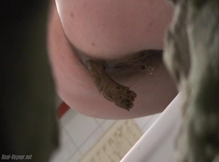 Женщина в длинном плаще какает в туалете