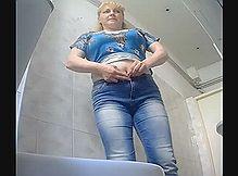 Женщину в туалете снимает скрытая камера с разных ракурсов