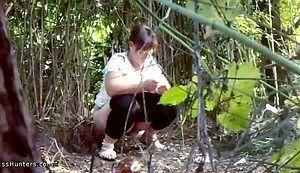 Пухленькая девушка притаившись писает в кустах